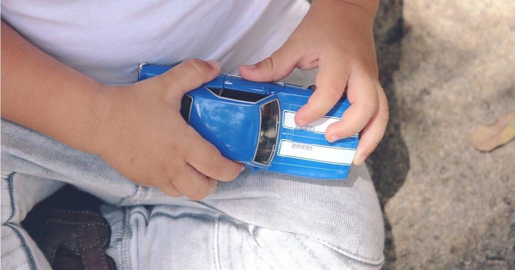 青いおもちゃの車と子供の手