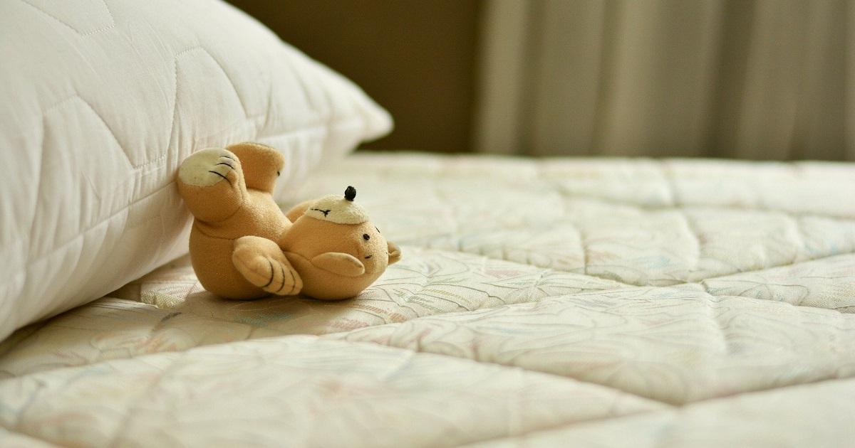ベッドの上に置いてあるクマのぬいぐるみ